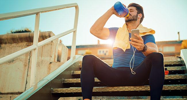Sportif qui consomme des BCAA dans un shaker après sa séance