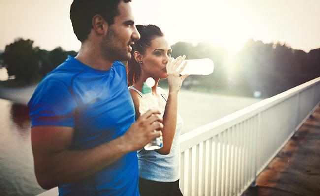 Joggeur et joggeuse se réhydratant après un footing
