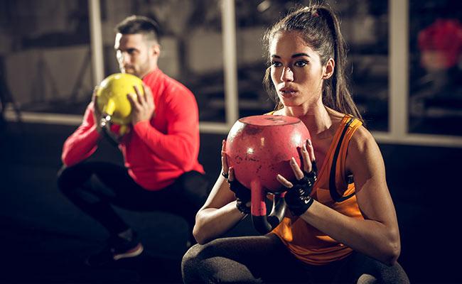 Homme et femme sportif en plein workout avec kettlebelt