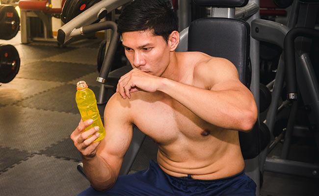 Sportif en salle s'hydratant