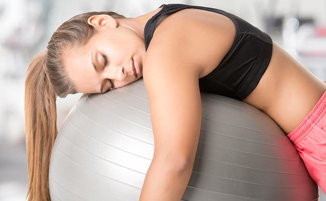 Jeune femme s'endormant sur son medecine ball