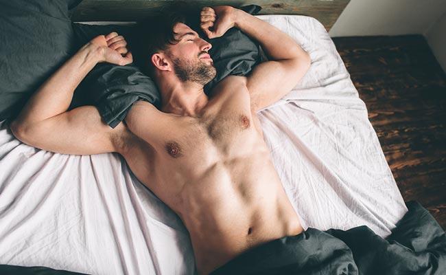 Jeune homme musclé se réveillant d'un sommeil profond