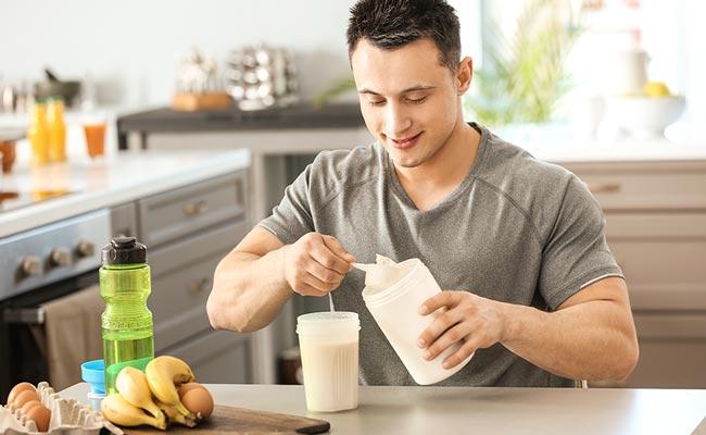 Jeune homme se préparant un shaker de protéine chez lui
